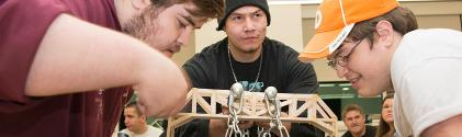 Three students build a bridge in physics