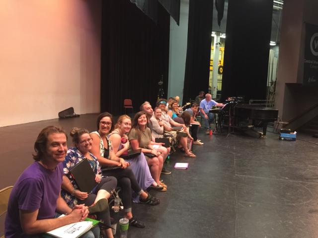 The cast of the retail song cycle sits on stage ready for rehearsal.