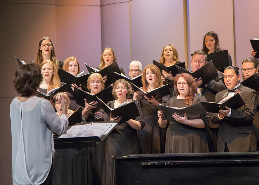 A choir sings in a performance on stage