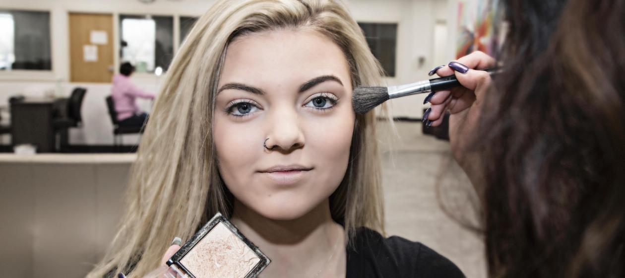 A student practices makeup application techniques