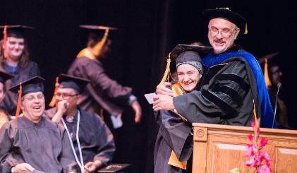 Dr. Brad Tyndall hugs a student at graduation