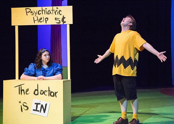 Actors playing Charlie Brown and Lucy at her psychiatry booth