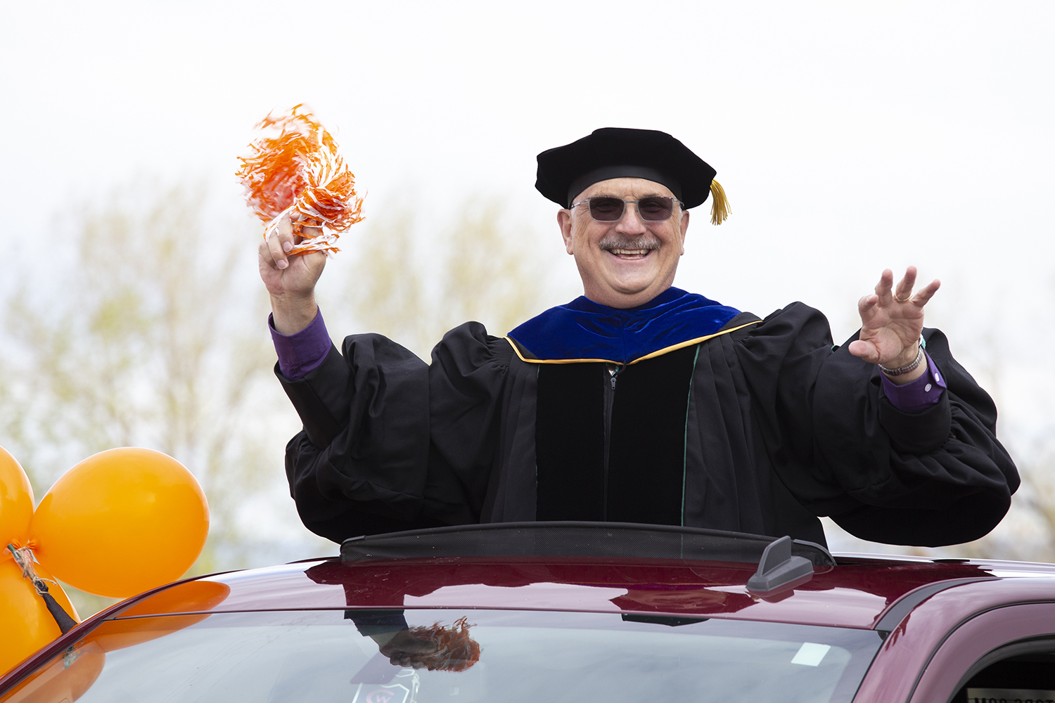 CWC President Tyndall stands through his truck's sunroof to cheer on graduates