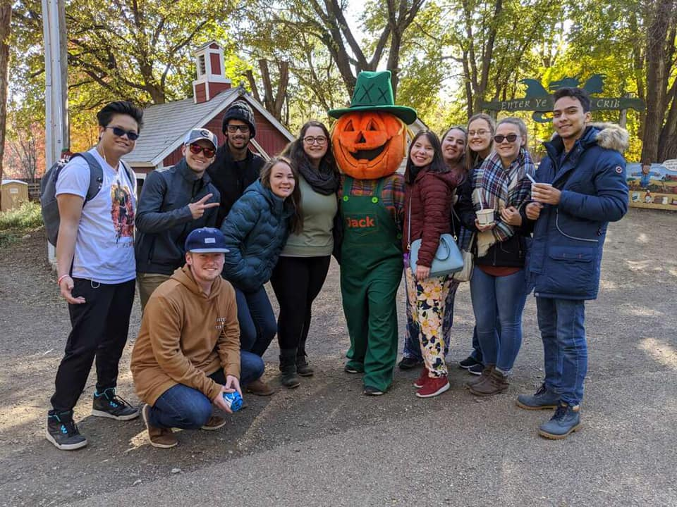 CWC students take a photo with a giant pumpkin at a pumpkin patch in Nebraska