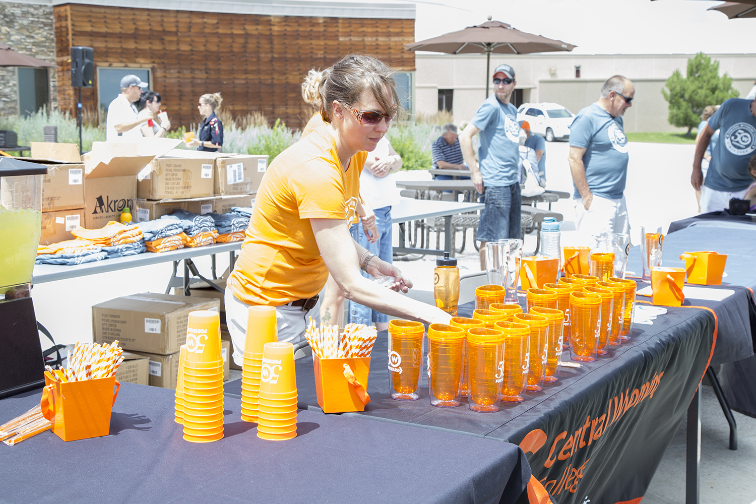 Woman setting up a table of orange CWC cups