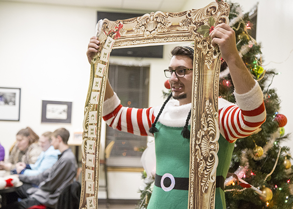 Student dressed as an elf posing while holding a fancy picture frame prop