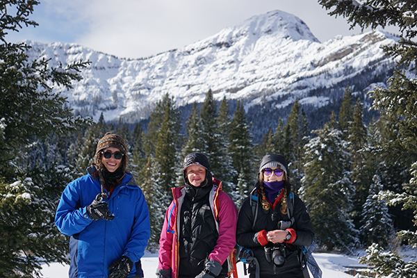 Three students posing in the winter with a snowy mountain in the background
