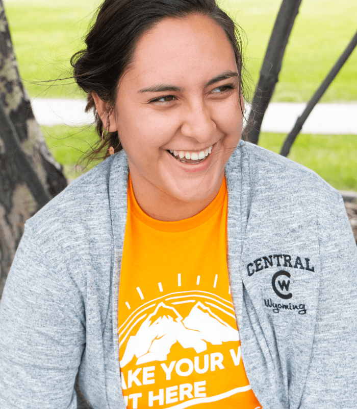 A student sits outside with CWC gear on