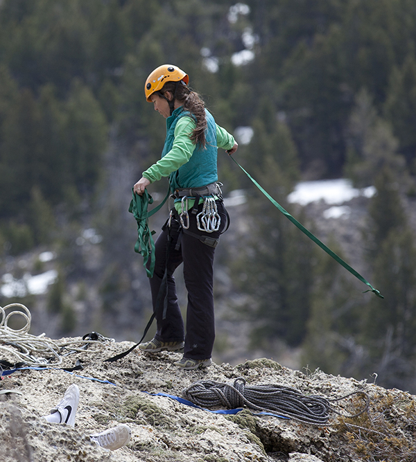 Stacy Wells in mountain climbing gear laying out a cable