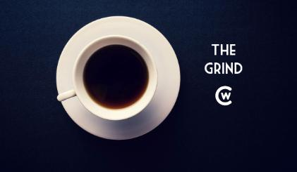 White coffee cup sits on a dark blue background with The Grind logo and CWC logo