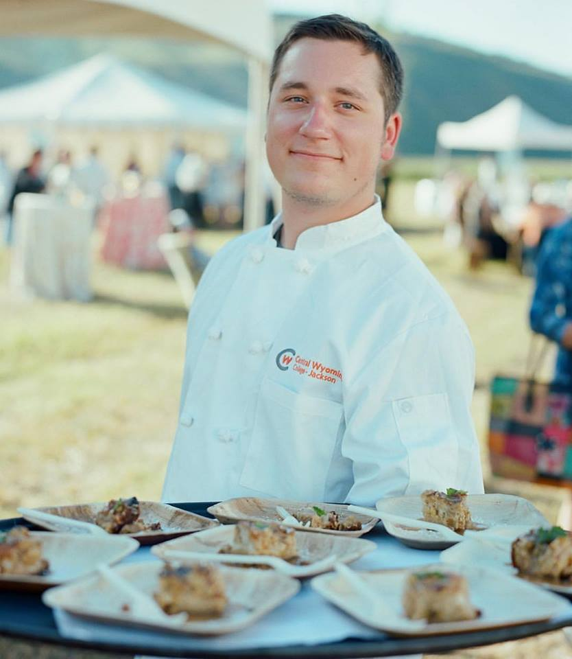 Zack Ward culinary student in smock in front of dessert table