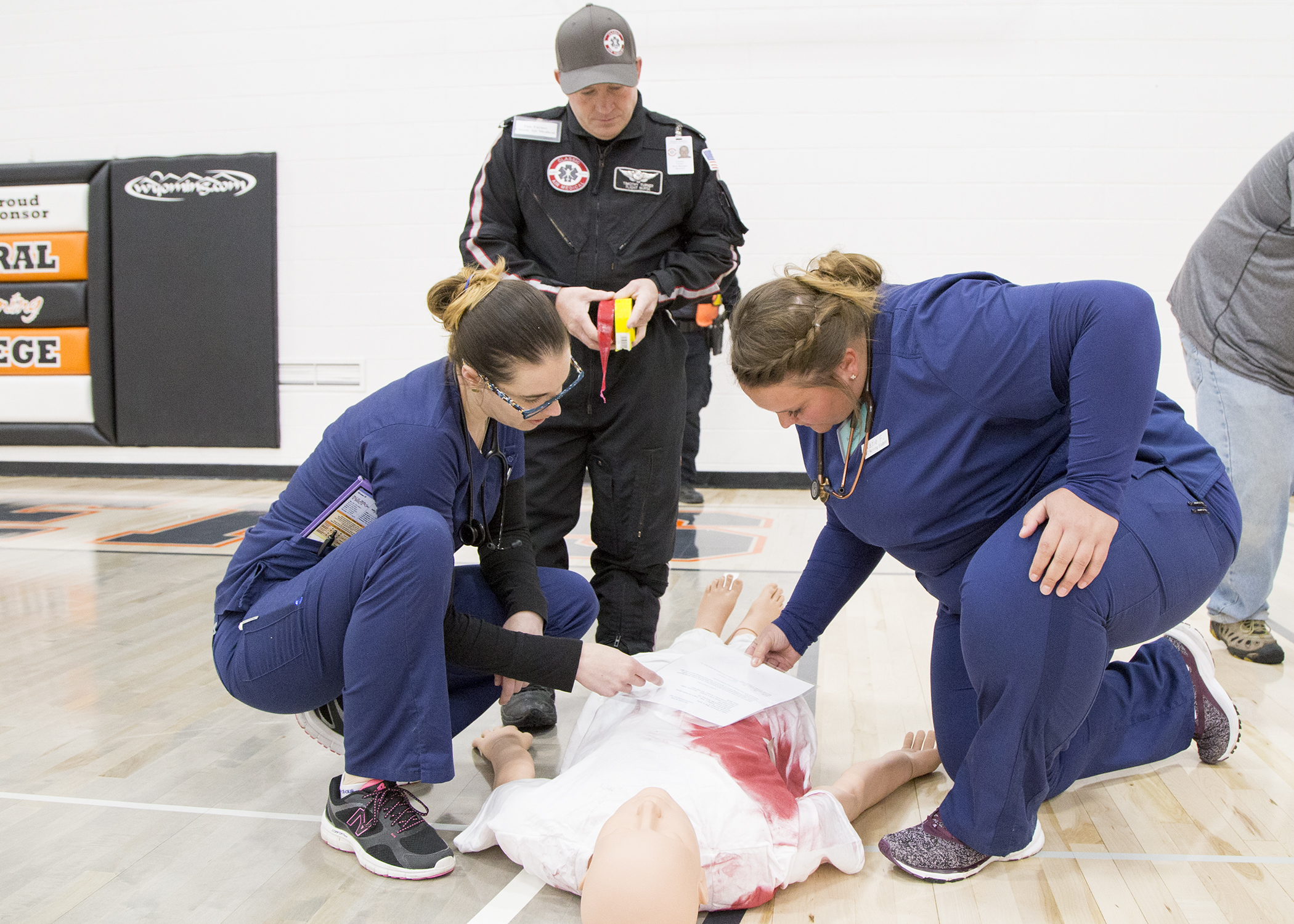 two nursing students look at a dummy for fake injuries while a flight for life medic assesses their work