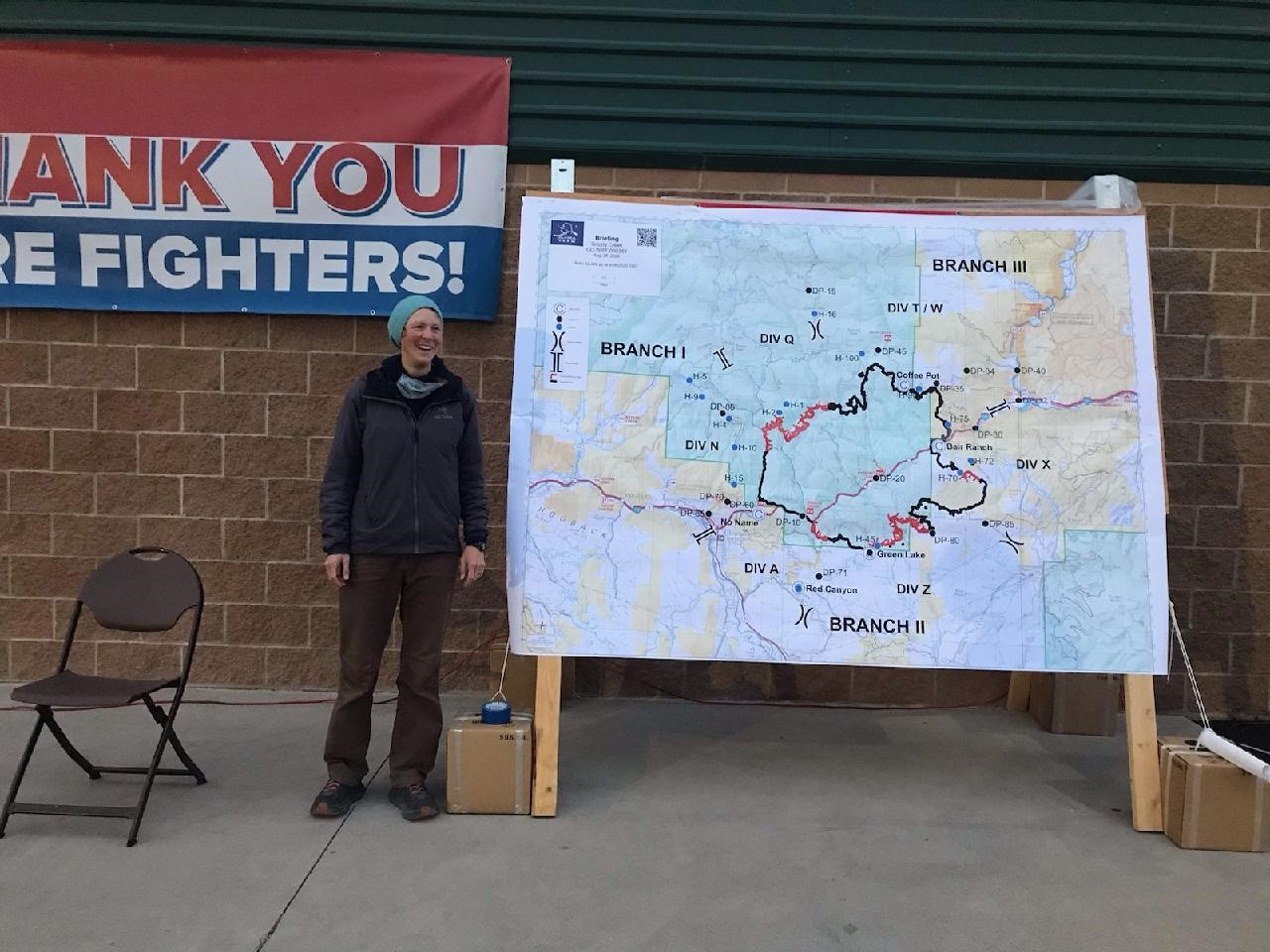 Sarah Strehle stands next to a map she uses for mapping fires with GIST