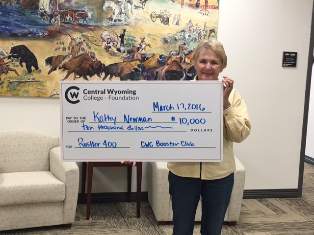 photo of Kathleen Newman holding her winning check from Rustler 400