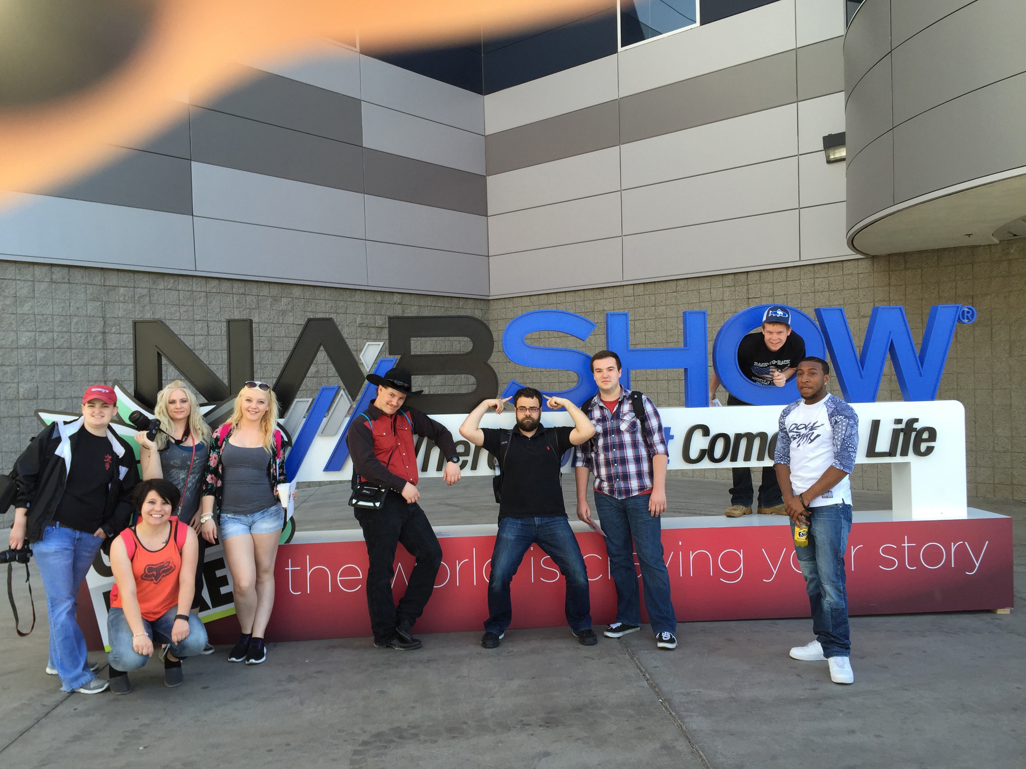 photo of Central Wyoming College students in front of the NAB show sign in Las Vegas during the NAB conference 2015