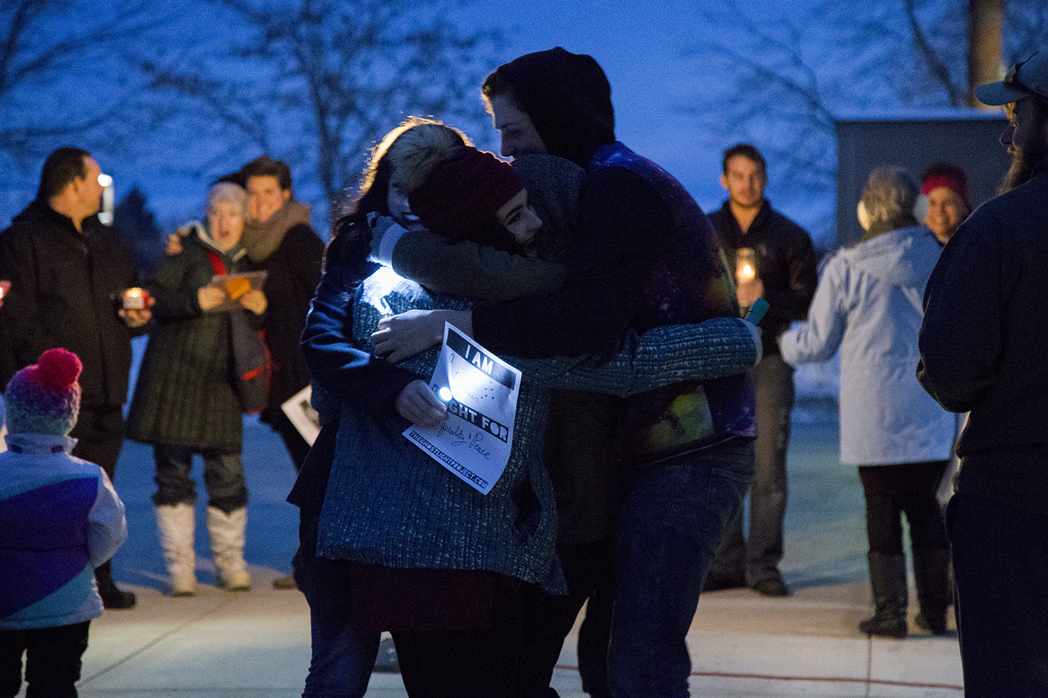 students hug at Ghostlight Project at dusk with flashlights in hand