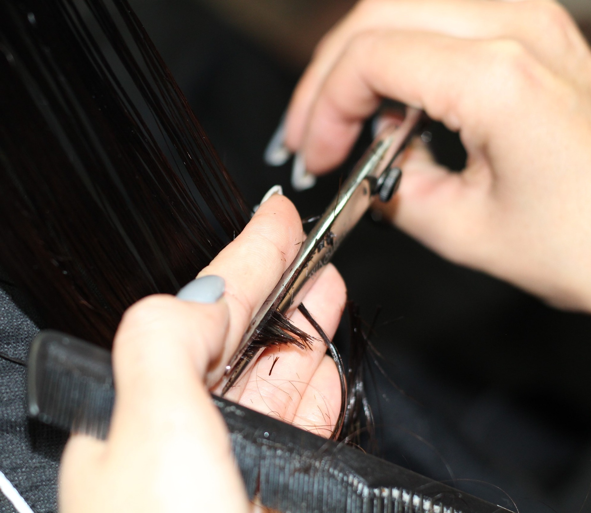 hairstylist holding scissors and a comb in their hands cutting hair