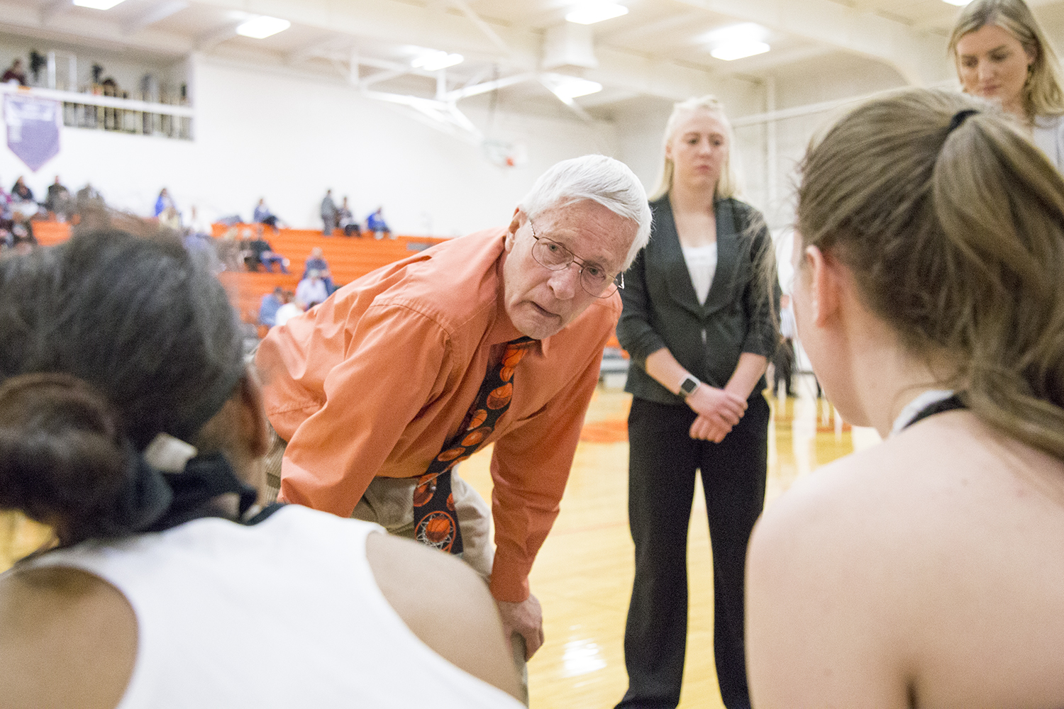 Coach Ken Swartz talks to his women's basketball team on the sidelines of a basketball game