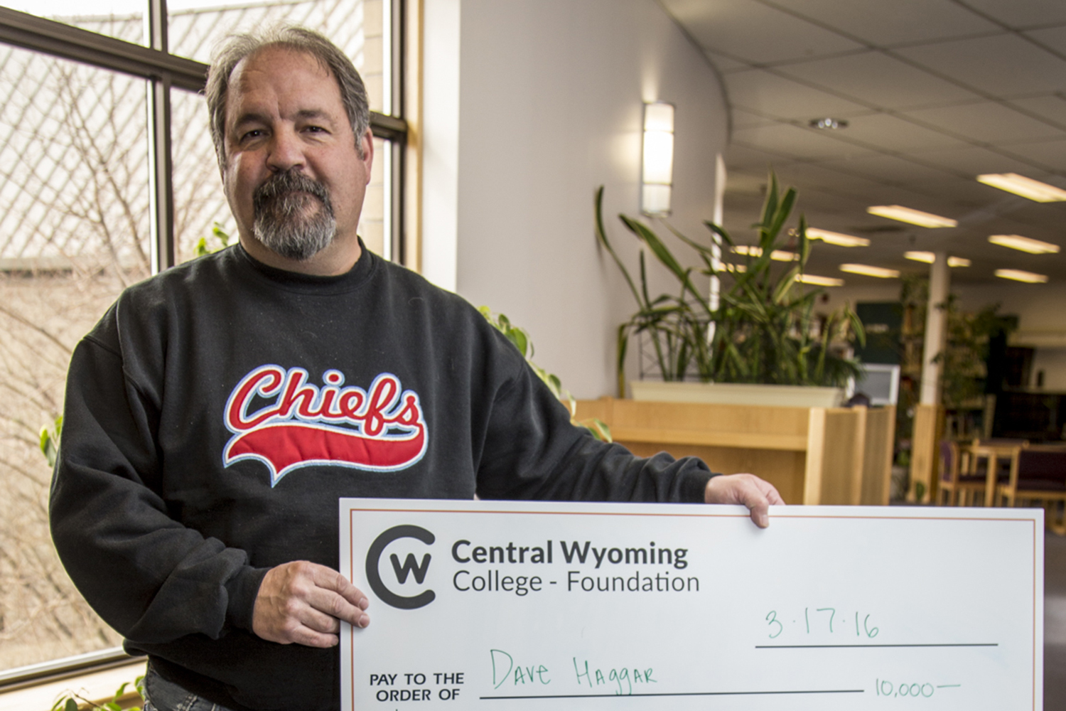 photo of the Rustler 400 winner, Dave Haggar holding a giant check of his winnings