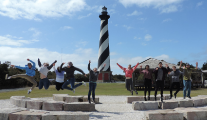 The Entrada club jumping in front of a lighthouse in North Carolina